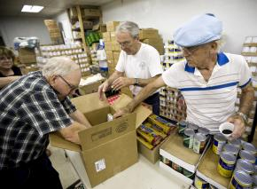Volunteers pack boxes of donated food for low-income families in Anderson, Calif.