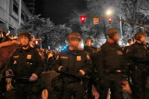 Riot police fill the street between the two parks held by Occupy Portland