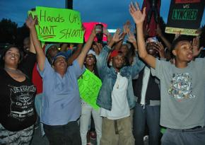 Residents gather in Ferguson, Mo., for an evening protest against police violence