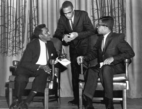 Bayard Rustin (seated at left) and Malcolm X (standing) at a debate in 1960