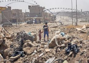 Children walk through the ruins of their neighborhood in Mosul