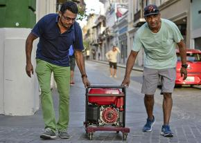 Residents roll a portable generator through the streets of San Juan