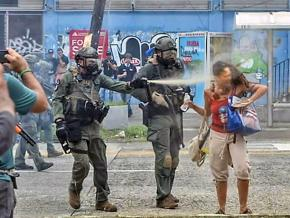 A riot cop in Puerto Rico assaults a May Day protester